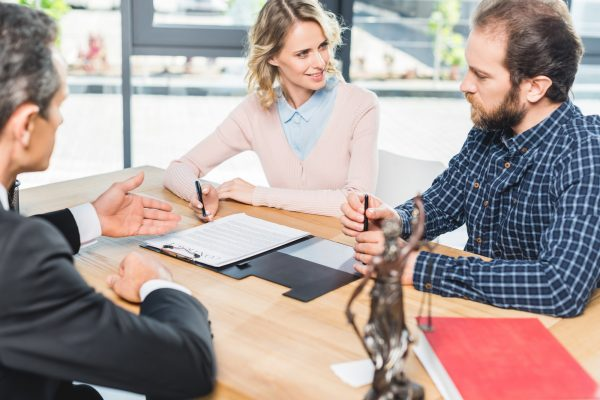 selective focus of couple discussing contract together with lawyer in office